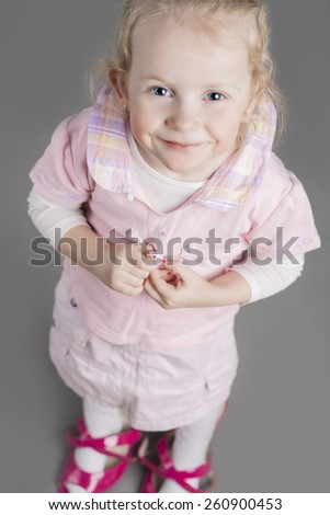Portrait of Young Caucasian Little Girl Trying On Mother's Shoes and Smiling. Vertical Image Composition - stock photo