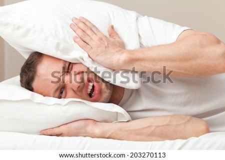 Portrait of Young Caucasian man in bed angry about noise  - stock photo