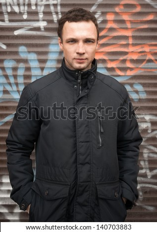 Portrait of young Caucasian man in black jacket with graffiti on a background - stock photo