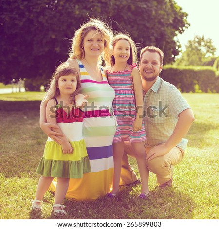 Portrait of young caucasian pregnant woman with her family in the meadow of the park. - stock photo