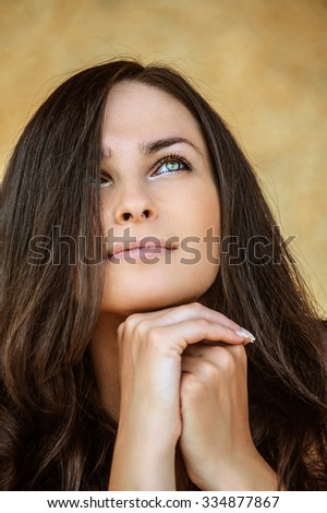 Portrait of young charming cheerful woman propping up her face against beige background. - stock photo