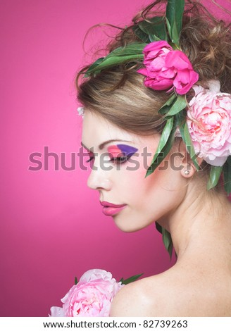 Portrait of young charming woman with  flowers in her hair on the pink background - stock photo