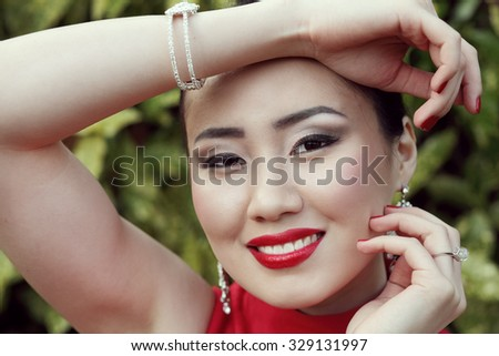 Portrait of young cheerful asian female wearing her luxury jewelry  - stock photo