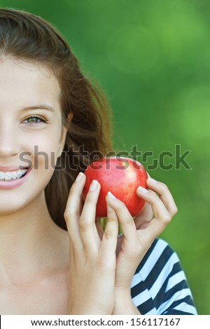 Portrait of young cheerful attractive smiling woman eating red ripe apple at summer green park. - stock photo