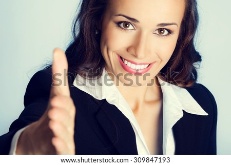 Portrait of young cheerful beautiful brunette businesswoman giving hand for handshake - stock photo