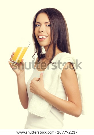 Portrait of young cheerful cheerful brunette woman drinking fresh lemon or orange citrus juice, in tank top casual smart clothing. Healthy lifestyle and dieting concept. - stock photo
