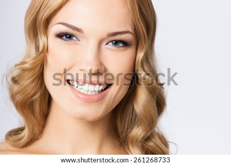 Portrait of young cheerful happy smiling woman, against grey background - stock photo