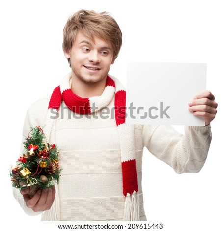 portrait of young cheerful smiling caucasian man which holding sign and christmas tree with nice smile - stock photo