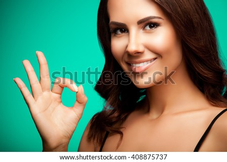 Portrait of young cheerful smiling woman showing okay gesture, over bright green background - stock photo