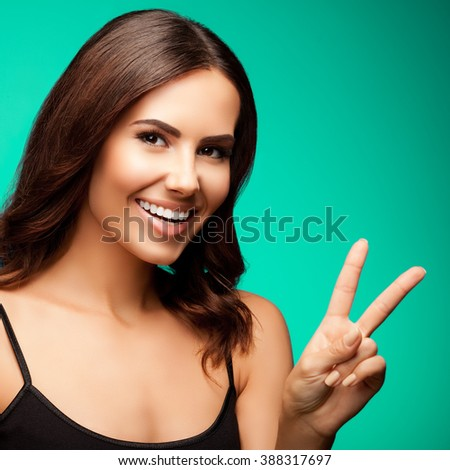 Portrait of young cheerful smiling woman showing victory gesture, over green background - stock photo