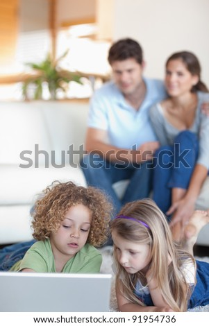 Portrait of young children using a laptop while their parents are watching in their living room - stock photo