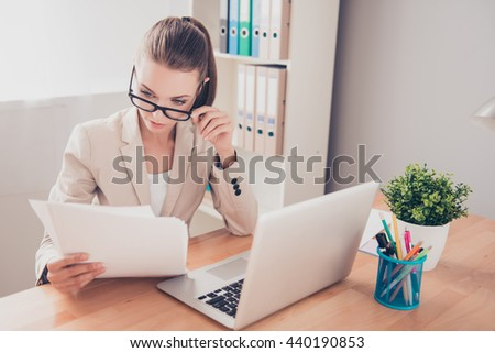 Portrait of young concentrated businesswoman in glasses reading contract - stock photo
