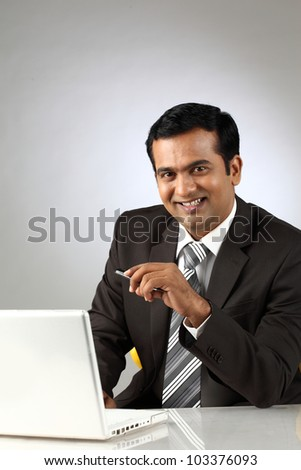 Portrait of young confident business man with laptop - stock photo
