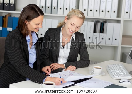 Portrait of young confident businesswomen sitting at office desk - stock photo