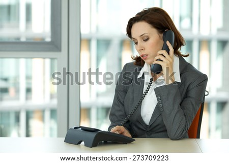 portrait of young confident caucasian businesswoman talking on phone - stock photo