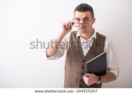 Portrait of  young confident man with tablet and glasses on grey background. - stock photo