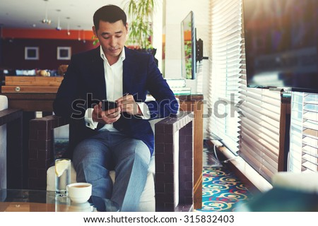 Portrait of young confident men entrepreneur dressed in luxury suit chatting on cell telephone during work break, intelligent male using his mobile phone while preparing for business meeting in office - stock photo