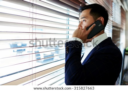 Portrait of young confident successful businessman dressed in elegant suit having mobile phone conversation, smart asian men entrepreneur talk on his cellphone while standing in office space interior - stock photo