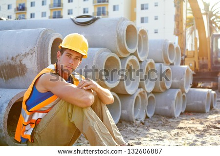 Portrait of young construction worker sitting down looking at camera - stock photo