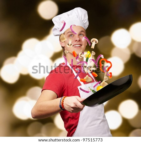portrait of young cook man cooking vegetables against a abstract background - stock photo