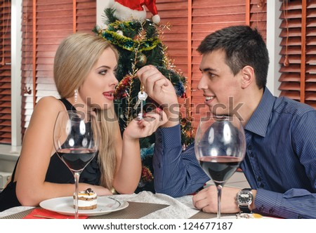 portrait of young couple about new year tree with glasses of wine - stock photo