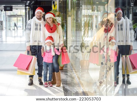 Portrait of young couple and their daughter in Santa caps looking at camera in the mall - stock photo