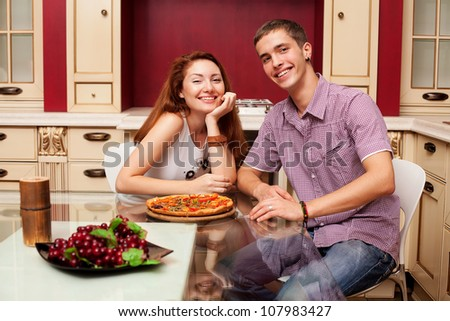 portrait of young couple cooking, in their kitchen happy smile - stock photo