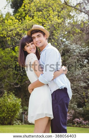 Portrait of young couple cuddling each other in garden - stock photo