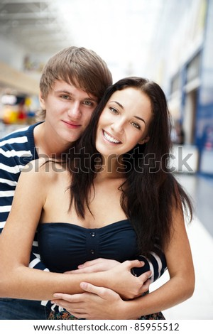 Portrait of young couple embracing at shopping mall and looking at camera. Vertical shot - stock photo