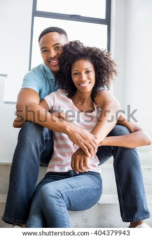 Portrait of young couple embracing on steps at home - stock photo