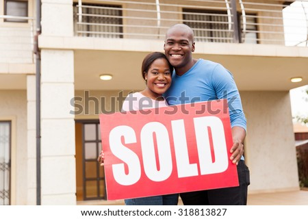 portrait of young couple holding sold sign outside their house - stock photo