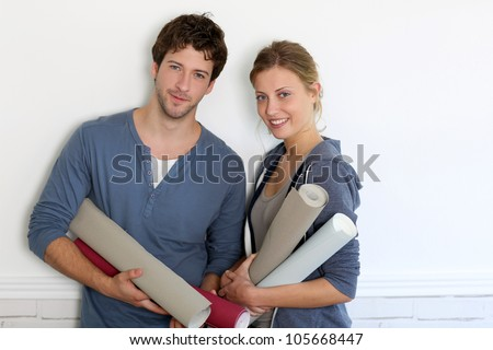 Portrait of young couple holding wallpaper rolls - stock photo