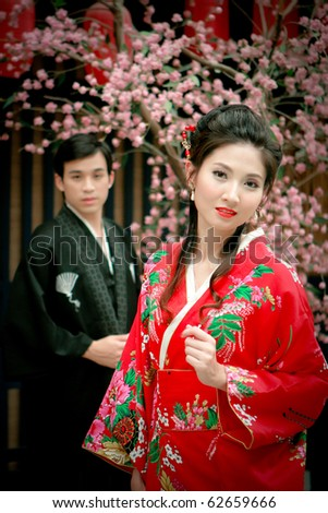 Portrait of young couple in japan dress looking for something - stock photo
