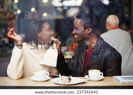 Portrait of young couple in love at a coffee shop, boyfriend wiping her mouth with a napkin at breakfast, romantic couple having fun together, two friends smiling sitting in cafe - stock photo