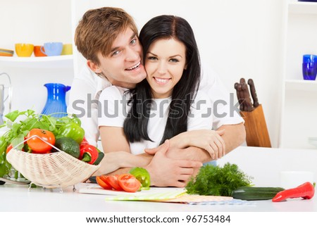 portrait of young couple in their kitchen hug, embracing happy smile, looking at camera - stock photo