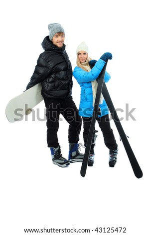 Portrait of young couple in warm clothes holding skis and snowboard. - stock photo