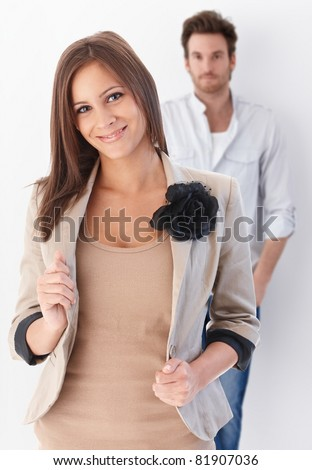 Portrait of young couple looking at camera, woman in front, smiling.? - stock photo