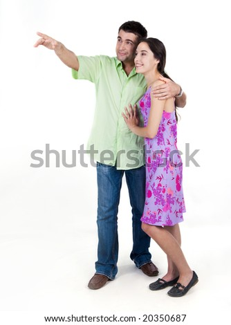 Portrait of young couple looking at something pointed at by man - stock photo