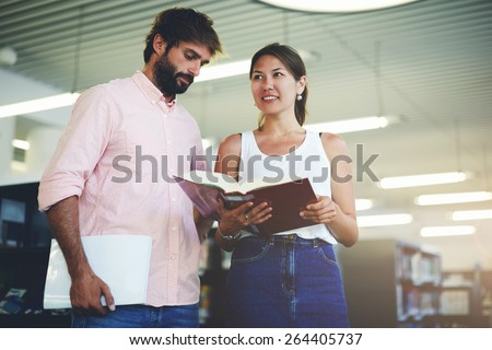 Portrait of young couple of students holding some books while preparing for university exams, business colleagues having fun while standing in modern work space, classmates studying in library, flare - stock photo