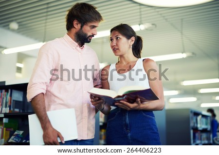 Portrait of young couple of students looking at each other while standing in the library, business colleagues having some flirtation while standing in modern work space, classmates in library - stock photo