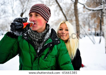 Portrait of young couple outdoor. Resting together in winter park - stock photo