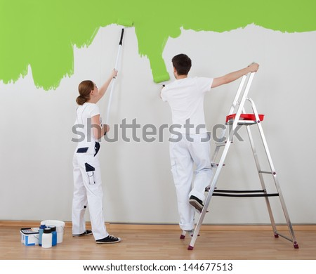 Portrait Of Young Couple Painting Wall Together - stock photo