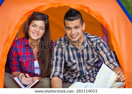Portrait of young couple sitting in a tent reading maps and planning their camping adventure - stock photo