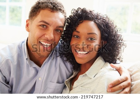 Portrait Of Young Couple Sitting On Sofa At Home - stock photo