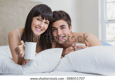 Portrait of young couple smiling and having cup of tea on bed in bedroom - stock photo