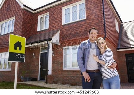Portrait Of Young Couple Standing Outside New Home - stock photo