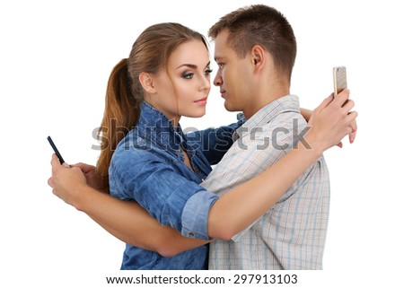 Portrait of young couple standing together and ignoring each other looking at smartphones. Relationship problems because of modern technologies and social networks concept. - stock photo