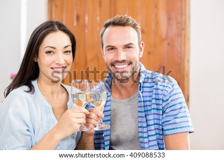 Portrait of young couple toasting wine glass at home - stock photo