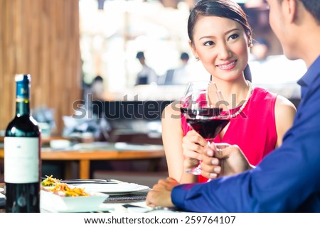 Portrait of young couple toasting with wine - stock photo