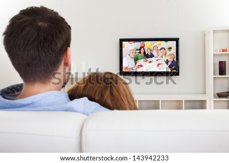 Portrait of young couple using laptop lying on bed - stock photo
